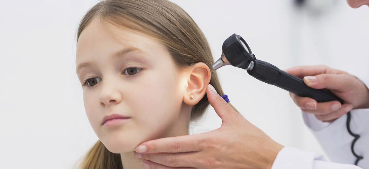 Doctor looking in ear of child